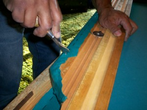 Removing staples holding the felt in place